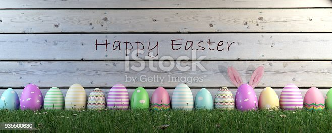 istock Colorful Easter Eggs On Grass With Happy Easter Text 935500630