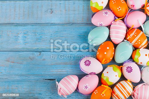 Colorful easter eggs on turquoise rustic wooden table