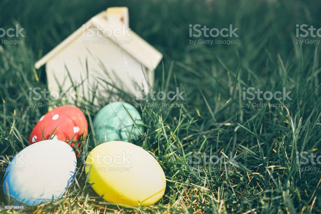 Bunte Ostereier mit einem Holzhaus in den Hintergrund auf dem grünen Rasen mit Morgenlicht verwischt. Dies ist ein soft-Fokus-Bild. – Foto