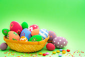 Group of colorful hand painted Easter eggs arranged in a wicker basket at the bottom of a green background leaving useful copy space for text and/or logo. Sugar sprinkles and candies complete the composition. High resolution 42Mp studio digital capture taken with Sony A7rII and Sony FE 90mm f2.8 macro G OSS lens