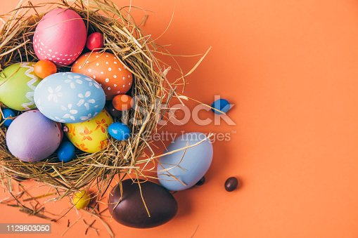 Easter eggs painted by children with chocolate and candies in a hay nest on a orange background. Top view