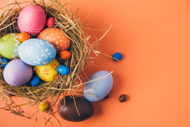 초콜릿 및 사탕 주황색 배경에 둥지에서 다채로운 부활절 달걀 - 부활절 달걀 뉴스 사진 이미지