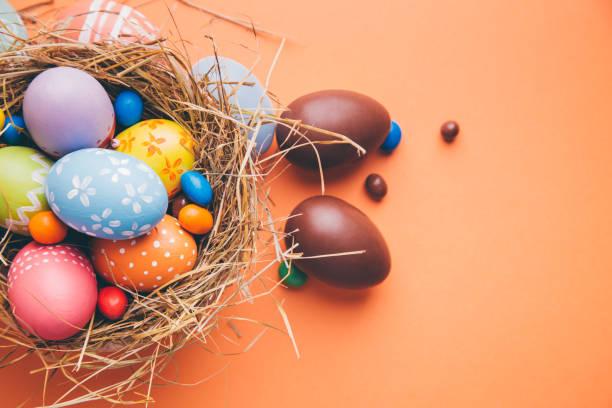 Bunte Ostereier mit Schokolade und Bonbons in einem Nest auf einem orangefarbenen Hintergrund – Foto