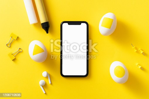 Colorful easter concept. Blank screen mobile phone with clipping path. Easter eggs, pushpins, binder clips and color pens on yellow background.