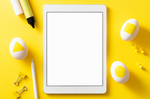 Colorful easter concept. Blank screen digital tablet with clipping path. Easter eggs, pushpins, binder clips and color pens on orange background.