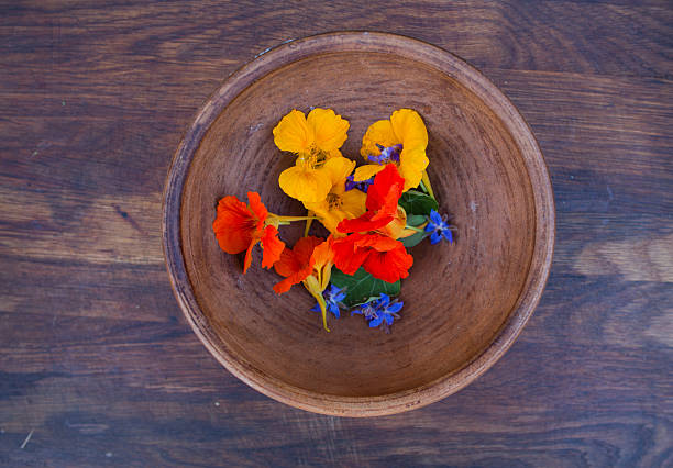 colorful edible flowers in clay bowl on wooden background - nasturtium stock photos and pictures