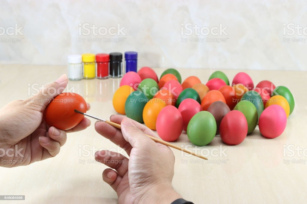 Colorful eggs are painted against paintbrush preparing easter day. stock photo
