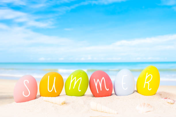 colorful eggs on white sand beach over blue background,happy Easter or summer holiday concept. stock photo