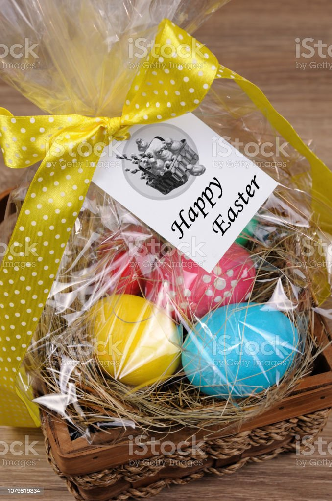 Colorful Eggs Stacked Hay In Cellophane Gift Basket For