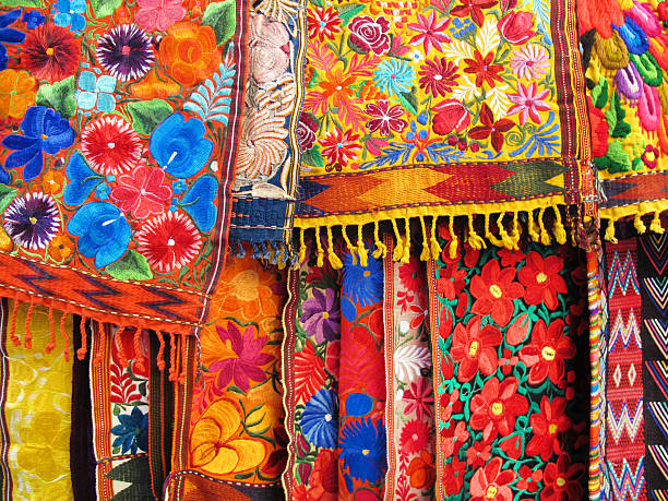 colorful embroidered fabrics in an outdoor market in mexico - aztekenmuster stock-fotos und bilder