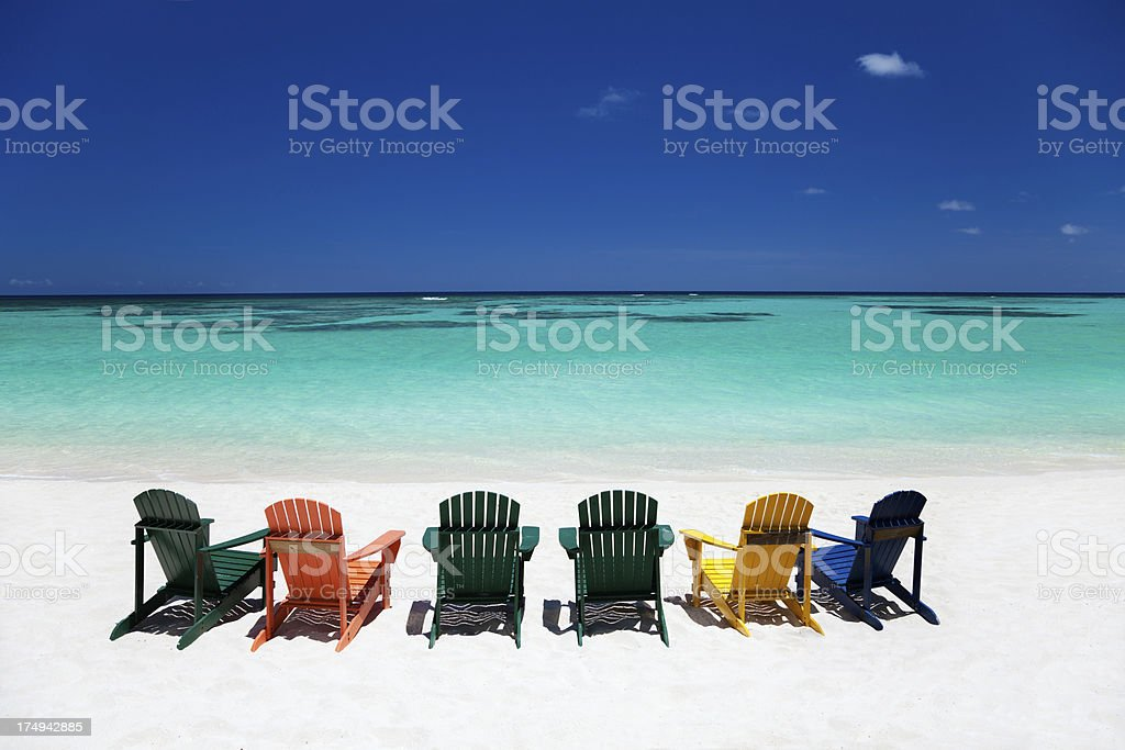 colorful empty adirondack chairs at a tropical Caribbean beach royalty-free stock photo
