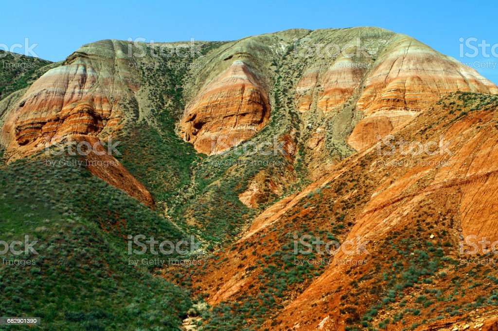 Colorful eroded cliffs with the green grassy slope stock photo