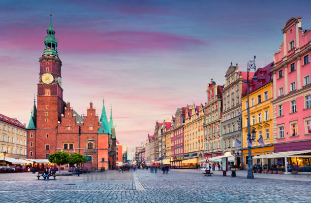 colorful evening scene on wroclaw market square with town hall. - poland stock photos and pictures