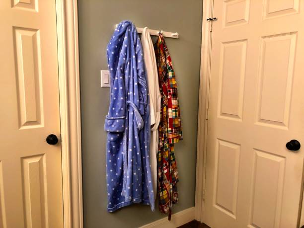 Colorful everyday bathrobes hanging on hooks in a home behind bathroom door stock photo