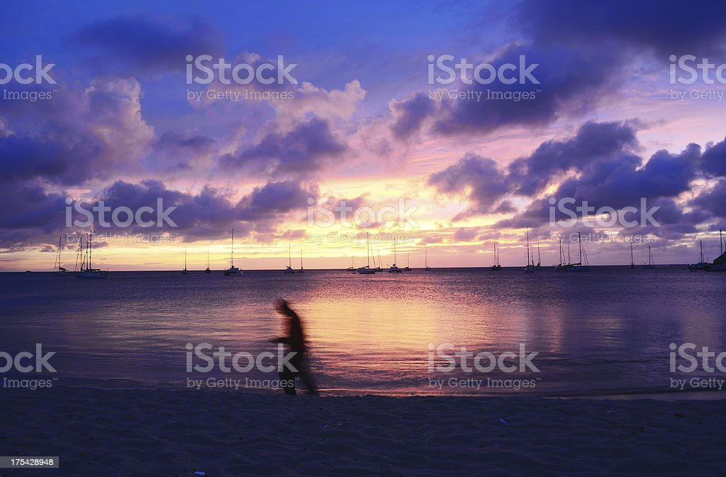 colorful exotic beach and sunset with lone walking person royalty-free stock photo