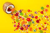 黄色背景色、創造的な静物、フラット レイアウト スタイルのココナッツ菓子のカラフルな爆発