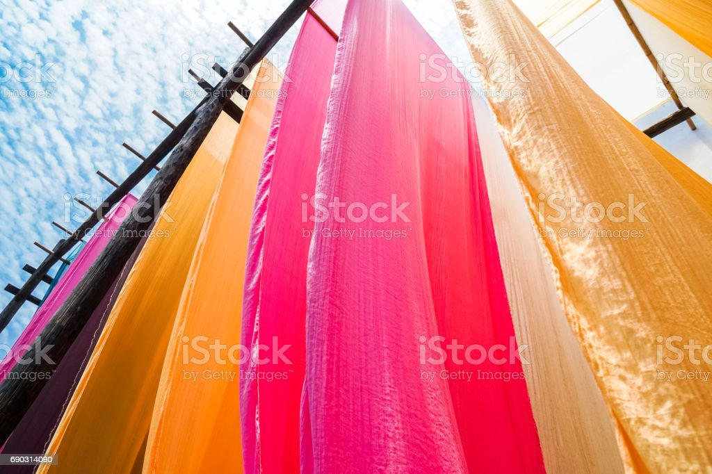 colorful fabric hanging to dry after traditional dye process stock photo