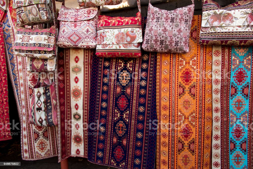 colorful fabrics and other folk products at a roadside stall with...