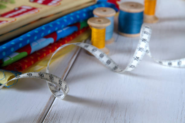 Cтоковое фото Colorful fabrics with pins, measuring tape and rolling cotton threads on white wooden table