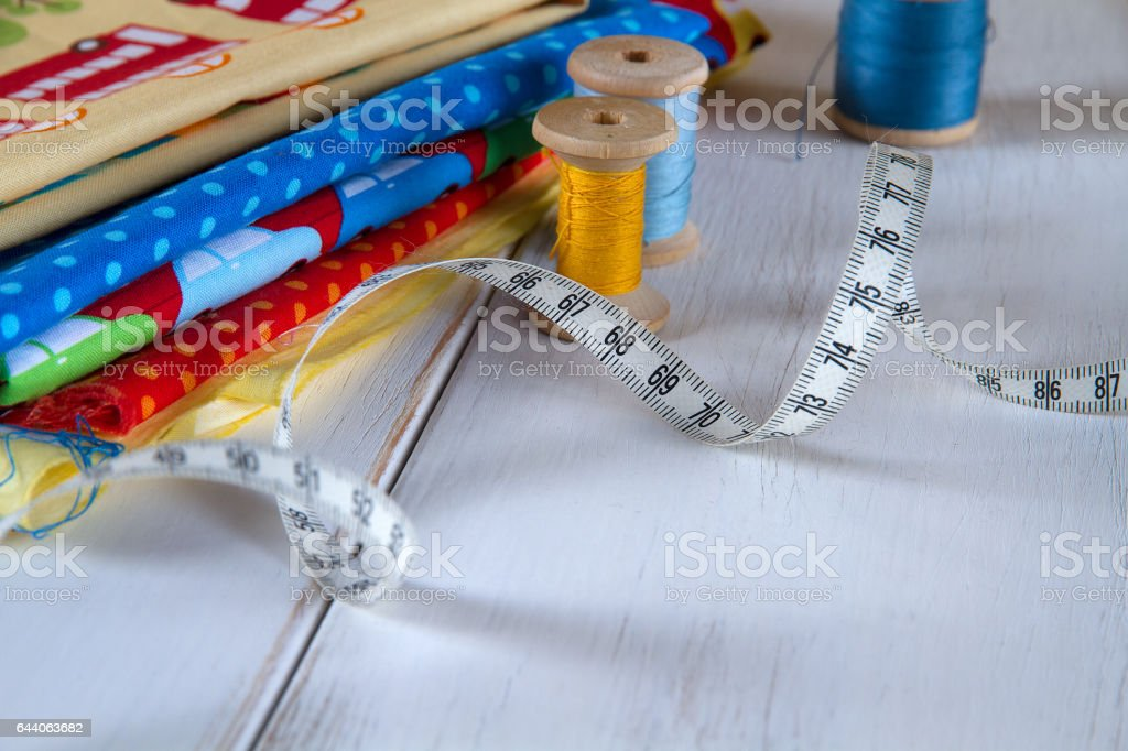 Colorful fabrics with pins, measuring tape and rolling cotton threads on white wooden table стоковое фото