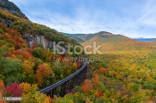 Aerial drone photo of during autumn day of the beautiful red, orange and yellow leaf foliage. Taken in the White Mountains, New Hampshire with train track trestle curving around mountainside.