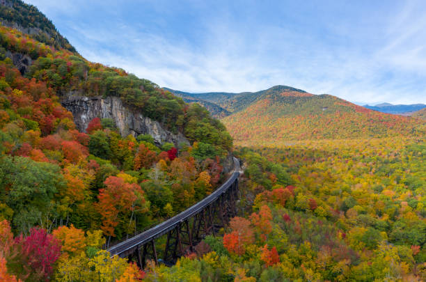 Colorful Fall Foliage in Mountains (Aerial View) Aerial drone photo of during autumn day of the beautiful red, orange and yellow leaf foliage. Taken in the White Mountains, New Hampshire with train track trestle curving around mountainside. white mountains new hampshire stock pictures, royalty-free photos & images