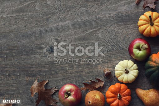 istock Colorful Fall Thanksgiving Harvest Background with Apples, Pumpkins, Pear Fruit, Leaves, Acorn Squash and Nut Border Over Dark Wood 865189842