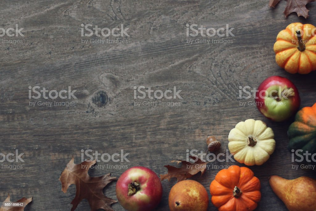 Colorful Fall Thanksgiving Harvest Background with Apples, Pumpkins, Pear Fruit, Leaves, Acorn Squash and Nut Border Over Dark Wood stock photo