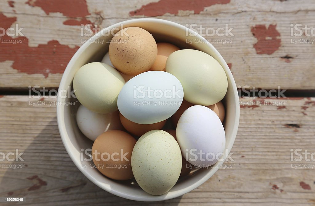 Colorful farm fresh eggs in bowl on wood plank floor stock photo
