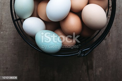 Multi-colored organic eggs from free range chickens on a rustic barn wood background.  Multi-colored organic eggs from free range chickens on a rustic barn wood background.  A brown, white, and a baby blue egg in a row.