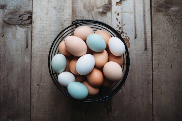 Colorful Farm Fresh Eggs on Rustic Wood Background stock photo
