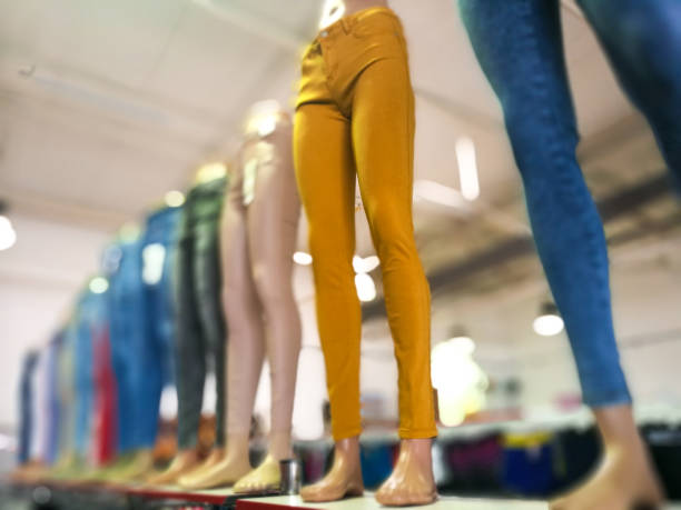 Colorful fashionable womens jeans and trousers on display in clothing store Color image depicting a selection of colorful womens denim jeans and trousers being modelled by plastic mannequins inside a clothing store. Lots of room for copy space. skinny pants stock pictures, royalty-free photos & images