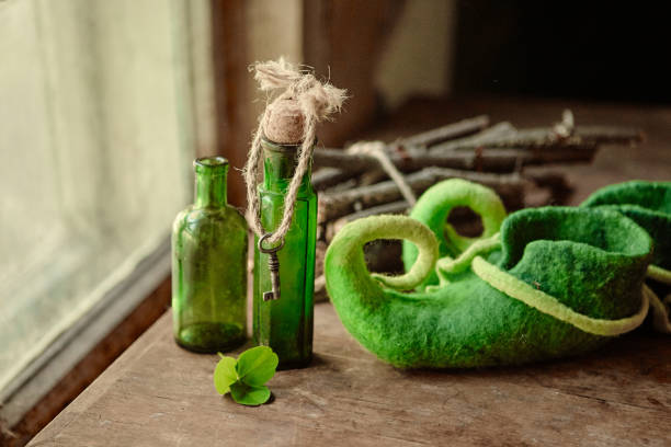Colorful felted green shoes stand next to antique glass bottles, a leaf of clover and a bundle of firewood stock photo