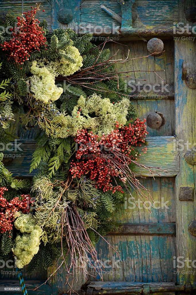 Colorful festive holiday wreath on an antique door royalty-free stock photo