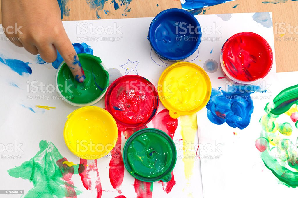 colorful finger paints on a table stock photo