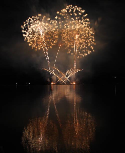 kolorowe pokaz sztucznych ogni z refleksji nad jeziorem. - new year zdjęcia i obrazy z banku zdjęć