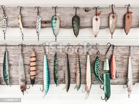 Colorful fishing baits on a wooden wall. Fishing equipment.