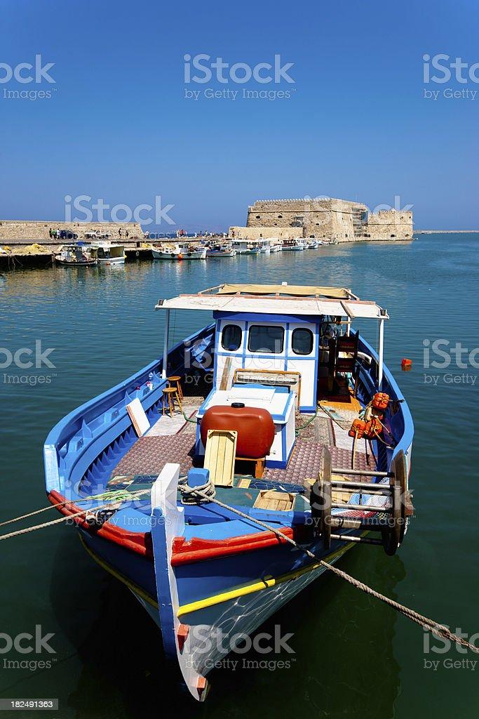 "Colorful Fishing Boat Iraklion Harbor Crete ""Fishing boat in the venetian harbor of Iraklion under a sunny blue sky, Unrecognizable tourists walking on promenade to famous Fortress Koules in the background. Iraklion,  Crete Island, Greece."" Crete Stock Photo"
