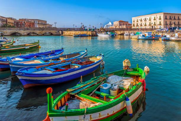bunte fischerboote auf dem wasser auf der insel ortigia mit dem stadtbild von syrakus in sizilien, italien - ortygia stock-fotos und bilder
