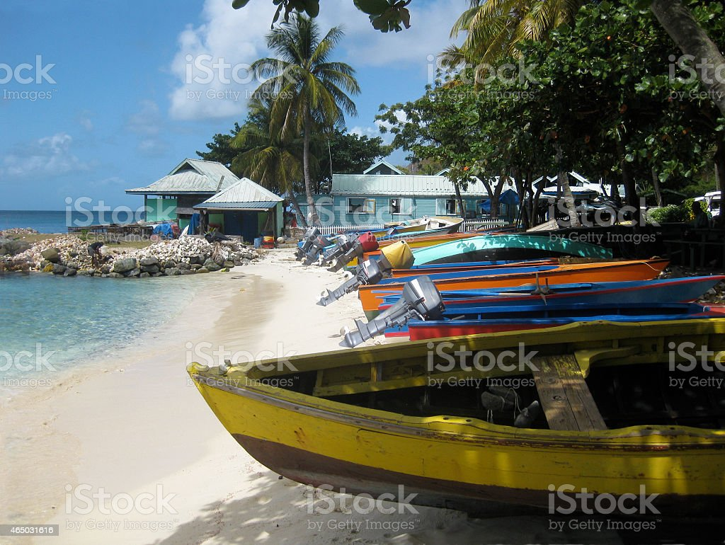 Colorful Fishing Boats on White Sand Beach in the Caribbean stock photo