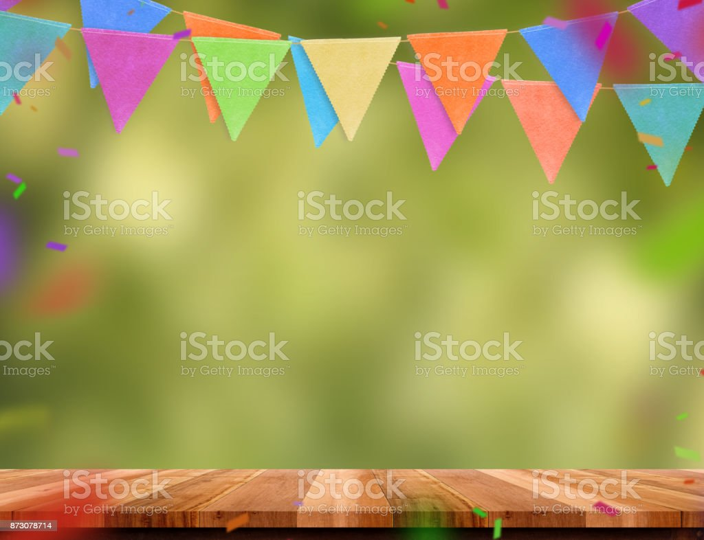 Colorful flag banner and confetti on wood table with blur green tree bokeh background, Template mock up for montage of product.party garland holiday backdrop for display design stock photo