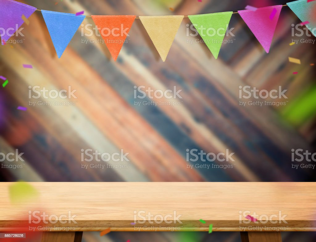 colorful flag banner bunting and confetti on wood table at diagonal wooden wall,Leave space for display or montage of your design, Holiday new year concept. stock photo