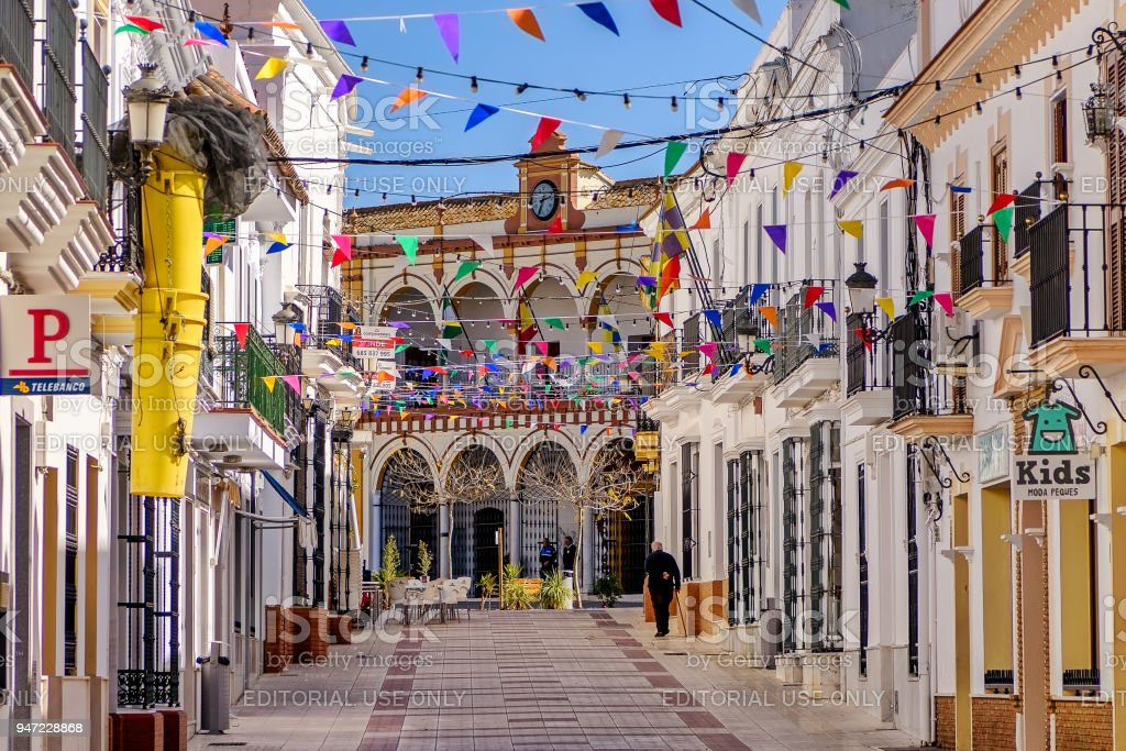 Colorful flags decorate the streets of old town Moguer in Huelva, Spain, during a local festivity. stock photo