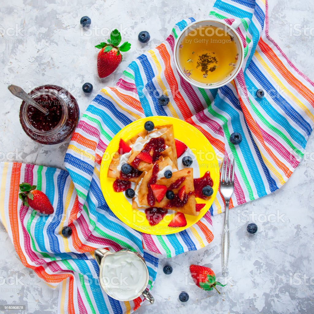 Colorful flat lay of two thin pancakes, folded in triangles, are poured with sour cream, jam and decorated with fresh berries. The concept of Russian holiday Maslenitsa stock photo
