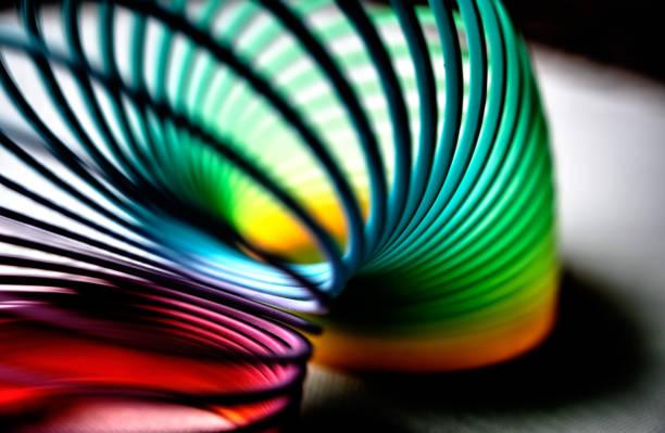 färgglada flexibla studsiga plastfjäder böjd i en båge - återhämtning bildbanksfoton och bilder