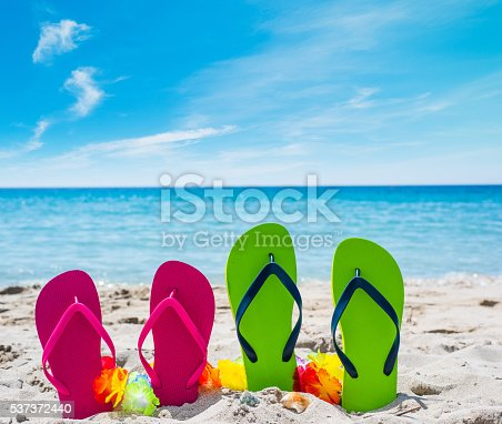 istock colorful flip flops on the sand 537372440