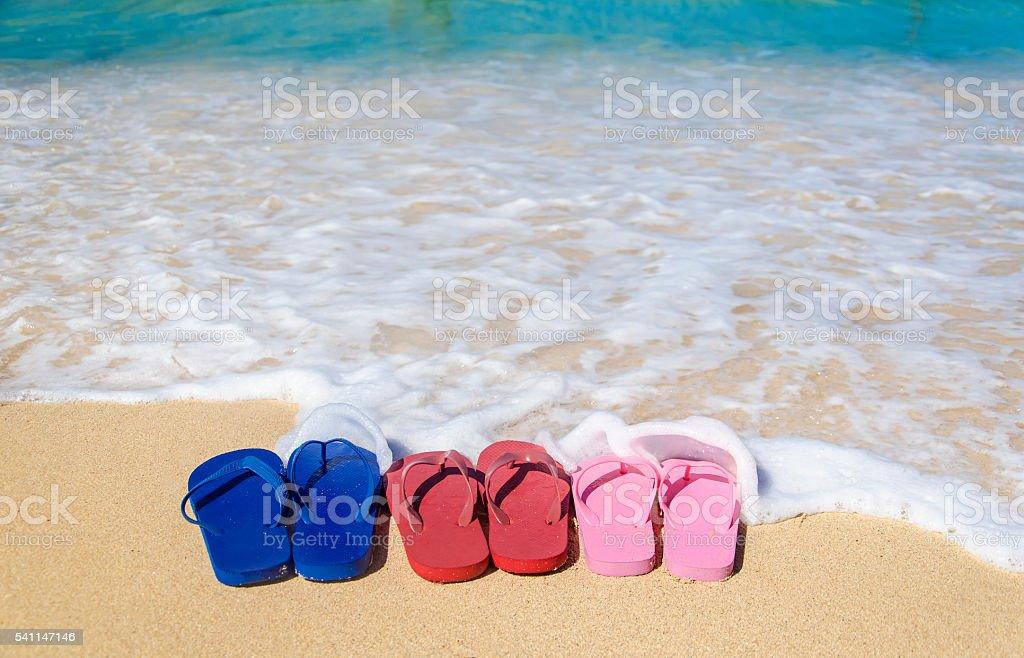 Colorful flip flops on the sandy beach stock photo