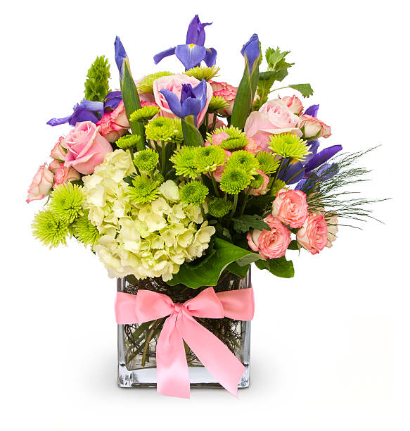 colorful floral bouquet in glass vase with pink ribbon isolated - bloemstuk stockfoto's en -beelden