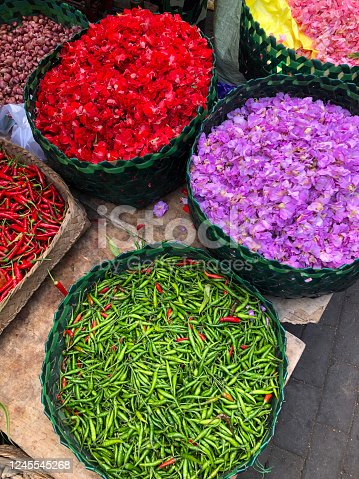Baskets of colorful flower petals and peppers for Hindu religious offerings, located in an open-air farmer's market in Bali, Indonesia