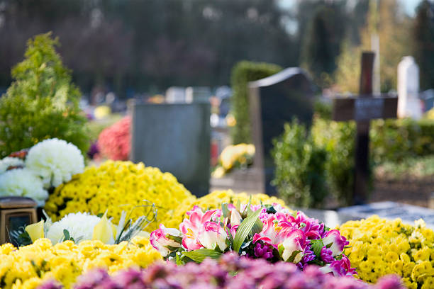 Colorful flowers and green trees on a graveyard stock photo